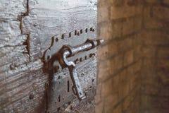 Järn låser på en gammal dörr i en fängelsehåla eller i en slott Royaltyfri Bild