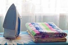Järn och en bunt av handdukar på strykbrädan, närbild, hushållsarbete royaltyfri foto