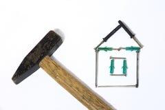 Järnhammaren med trähandtaget spikar huset på vit bakgrund arkivfoto