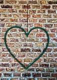Järnhjärta som hänger på en tegelstenvägg royaltyfri fotografi