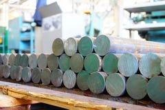 Järnkubbar är i materiel och ordnar till för att bearbeta med maskin på maskinhjälpmedel, ett lager av stålprodukter royaltyfria bilder
