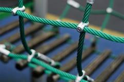 Järnskarvpunkt av rep i barnspindelrengöringsduk med skruven Detaljen av korsgräsplan ropes i säkerhet som klättrar utomhus- utru Arkivfoto