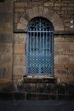 Järnskyddsgaller över gammalt välvt fönster Royaltyfri Fotografi