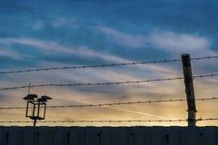 Järnstaket med blå himmel och solnedgång arkivbild