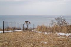 Järnstaket och höstfält på bakgrundshavet Förbjudet tillträde till den offentliga stranden royaltyfri fotografi
