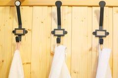 Järnsvart hakar för kläder på träväggen arkivbild