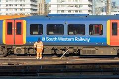 Järnväg anställd som är främst av det rörande drevet arkivfoto