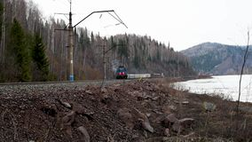 Järnväg bortgång längs flodbanken med ett gammalt elektriskt drev som flyttar sig in mot arkivfilmer
