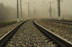 Järnväg för elektriskt drev En slät vänd som går in i dimman Arkivbild