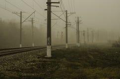 Järnväg för elektriskt drev En slät vänd som går in i dimman Royaltyfria Bilder