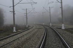 Järnväg för elektriskt drev En slät vänd som går in i dimman Royaltyfri Foto