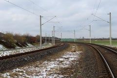 Järnväg i snö med blå himmel Arkivfoto