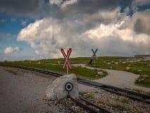 Järnväg korsning för kugghjul med Sts Andrew kors nära Hochschneeberg med molnig himmel i den sceniska solnedgången royaltyfri fotografi