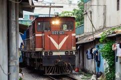 Järnväg linje bortgång mellan smala byggnader i den gamla fjärdedelen av Hanoi Royaltyfria Bilder