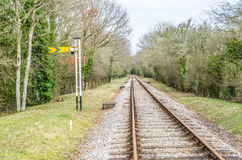 Järnväg linje för enkelt spår med den gula signalen Royaltyfri Fotografi