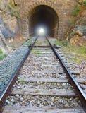 Järnväg med ljus på slutet av tunnelen. Arkivbilder