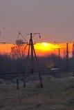 Järnväg som går till den milda solnedgången Royaltyfria Bilder