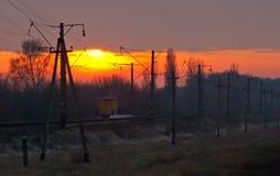 Järnväg som går till den milda solnedgången Arkivbilder