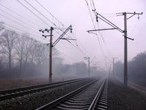 Järnväg stänger för spår för elektriskt drev med service och trådar på invallningen royaltyfria foton