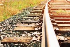 Järnväg trälängsgående stödbjälke och stänger på solnedgången royaltyfria bilder