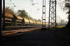 Järnväg vagnar som väntar i solnedgången Arkivbild