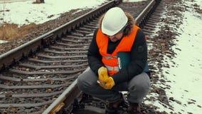 Järnvägarbetare med den justerbara skiftnyckeln för dokumentation stock video