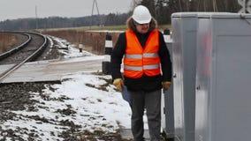 Järnvägarbetare med dokumentation nära elektrisk bilaga lager videofilmer