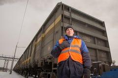 Järnvägarbetare med vagnen på bakgrunden Arkivfoton