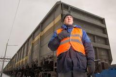 Järnvägarbetare med vagnen på bakgrunden Royaltyfria Bilder