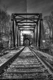 Järnvägbro som leder till en drevtunnel Arkivfoto