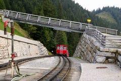 Järnvägen med ett drev under bron på bergsikten Arkivbild