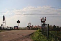 Järnvägkorsning med barriärer och röda ljus med det intercity drevet för ICM-koploper på Moordrecht i Nederländerna royaltyfria foton