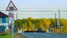 Järnvägkorsning med vägmärket mot gul skog lager videofilmer