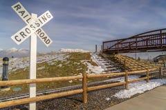 Järnvägkorsning tecken och bro mot berget arkivfoto
