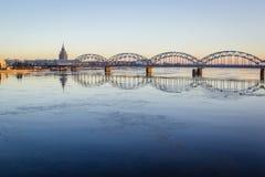 Järnvägsbro över den djupfrysta floden i den snöig vintern Riga under solen Royaltyfri Foto