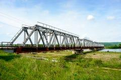 Järnvägsbro över floden, som flödar från bergen in Arkivfoto
