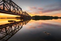 Järnvägsbro av stålkonstruktion i ljuset av inställningssolen Arkivfoton