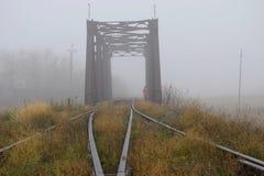 Järnvägsbro i dimman och en ensam passerby arkivbild