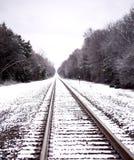 Järnvägspår i snön som leder in i oändlighet arkivfoto