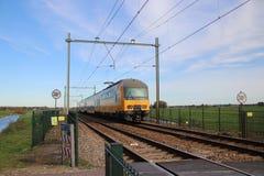 Järnvägspår med det gula blåa holländska drevet för dubbel däckare mellan gouda och Rotterdam på Moordrecht arkivfoton