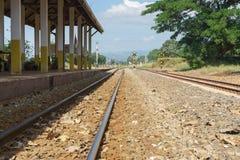 Järnvägspår och plattform med berg- och himmelbakgrund Arkivfoto