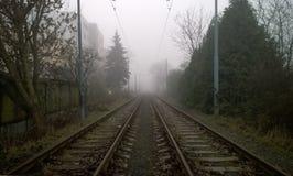 Järnvägspår som täckas delvist i dimma Arkivfoton