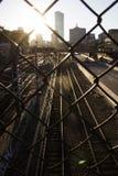 Järnvägspår till och med ett staket Arkivfoto
