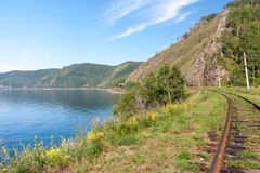 Järnvägsspår i natur i bergen nära den blåa sjön arkivfoto