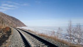 Järnvägsspår på kusten av Lake Baikal i vinter och vår Soligt väder i snöig Sibirien Vandring på denBaikal järnvägen royaltyfri bild