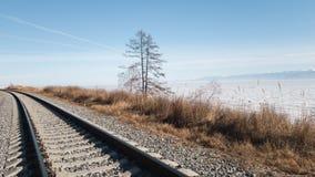 Järnvägsspår på kusten av Lake Baikal i vinter och vår Soligt väder i snöig Sibirien Vandring på denBaikal järnvägen arkivbilder