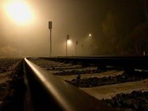 Järnvägsspår på midnatt under dimmigt väder arkivbild
