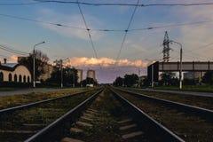 Järnvägsspår som går i riktningen av en härlig solnedgång arkivbild