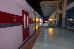 Järnvägsstation med det moderna drevet i nattetid royaltyfria bilder