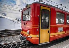 Järnvägsstationen med den röda schweizaren utbildar och berg i Jungfrau, Royaltyfri Foto
